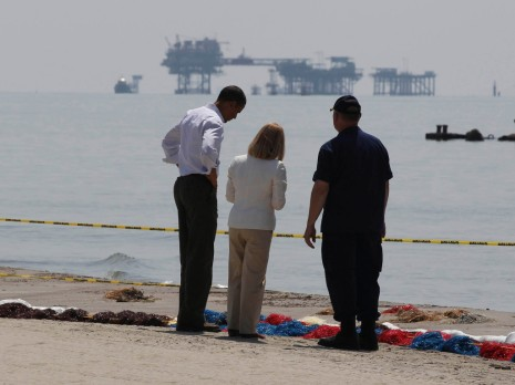 U.S. President Obama walks along the Louisiana coastline while touring damage caused by oil spill
